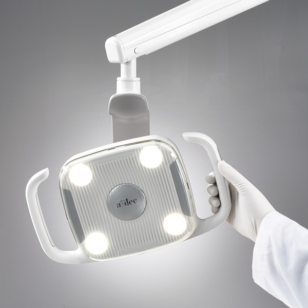 A hand positioning the A-dec 300 dental light
