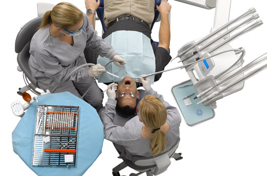 Dentist and assistant use dental delivery system with patient